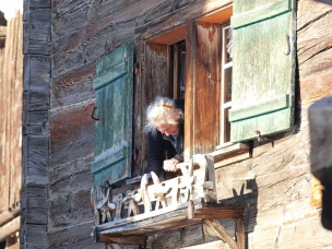 Veulden, old villager in a traditional sawlog house feeding the birds.